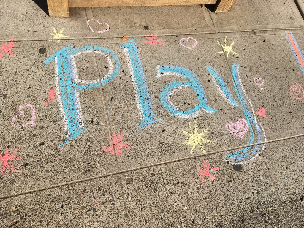 """Colorful blue chalk on the sidewalk reads """"Play"""" surrounded by small pink chalk hearts and yellow and red starbursts"""