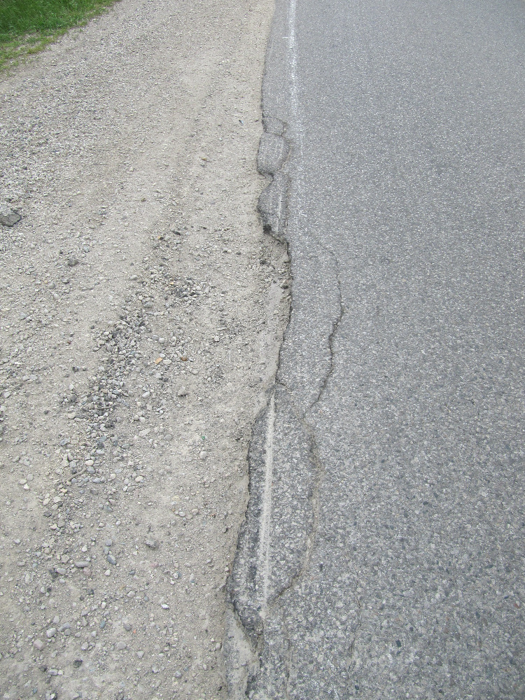 View of the breaking away of the east edge of the pavement at the apex of the north curve on Clarke Road north of Fanshawe Park Road in London.
