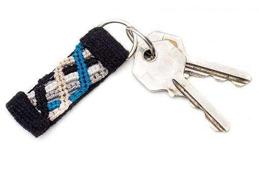 Small blue macrame keychain on black handwoven fabric