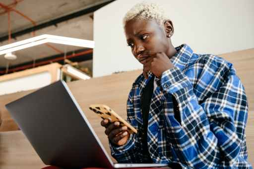 thoughtful black woman using smartphone and laptop