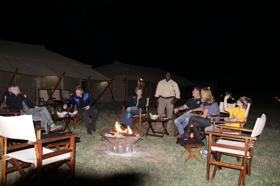 Safari guests gathered around evening bonfire. 8 Tips to See the Best of the Great Migration Calving Season. Gosheni Safaris