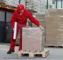 man-in-red-outfit-and-hard-hat-wrapping-plastic-around-boxes