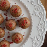 Peanut butter energy balls on plate with freeze dried strawberries