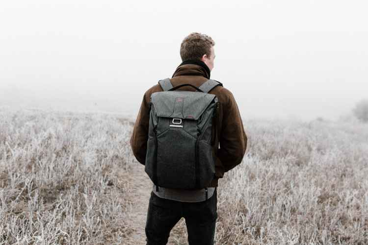 man standing on field carrying a backpack