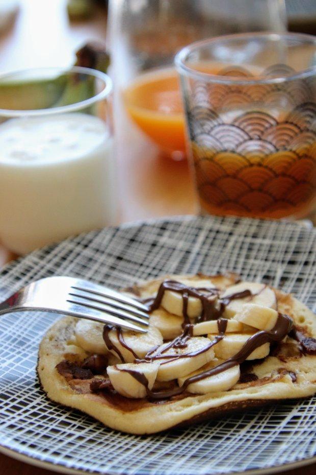 Petit déjeuner avec des pancakes moelleux au pépite de chocolat recouvert de banane