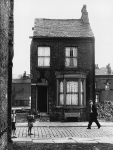A rather sad lone survival of a Victorian Terrace in Moss Side, Manchester. The floral curtains seem to show that this building is still being occupied, although the open cellar window, lack of front door and broken glass suggest the fate of this building may already be set. Photograph by Shirley Baker Date: 1964