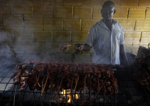 In this photo taken on Saturday, Oct. 20, 2012, a man grills meat to make suya in Lagos, Nigeria. As night falls across Nigeria, men fan the flames of charcoal grills by candlelight or under naked light bulbs, the smoke rising in the air with the smell of spices and cooking meat. Despite the sometimes intense diversity of faith and ethnicity in this nation of 160 million people, that thinly sliced meat called suya, is eaten everywhere. (AP Photo/Sunday Alamba)