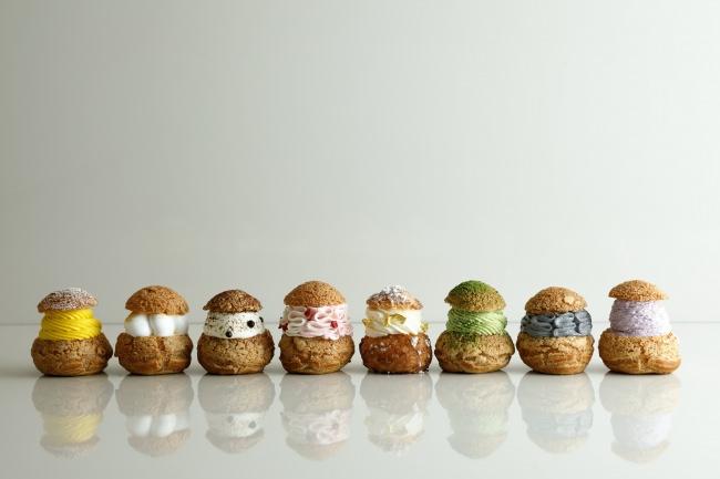 8 種類のシュークリーム(左から、マンゴー&パッションフルーツ、シトロン、ティラミス、ラズベリー&ライチ、バニラ、抹茶、セサミ、ブルーベリー&ヨーグルト)