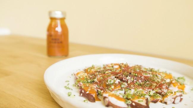 タコの韓国風カルパッチョ:薄切りのタコに「韓国風甘辛酢味噌」をかけ、小口切りのネギとニラ、白ごま、糸唐辛子を散らし、ごま油を回しかけます