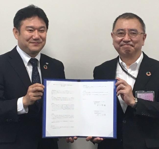 調印式の様子、ワタミの清水邦晃社長(左)、豊島区の金子智雄教育委員会教育長