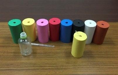 図1:実験で用いられた各色彩条件の容器。透明のペットボトルを色画用紙の筒で包装し、水溶液が直接見えないようにした。
