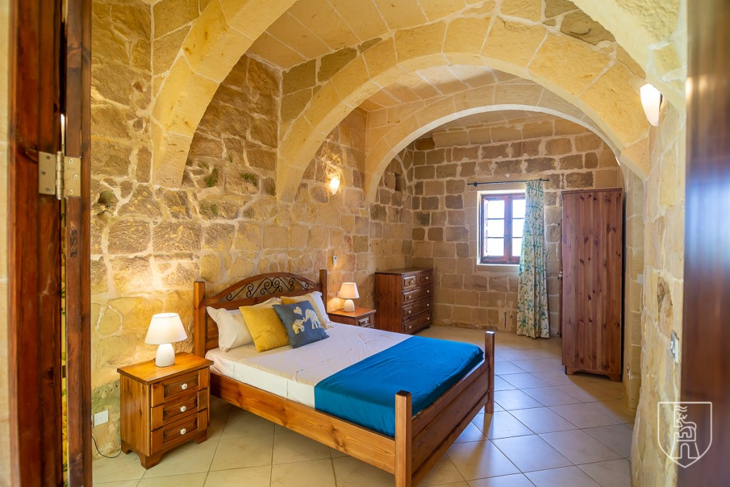 A bedroom in a traditional farmhouse, showing the traditional arch in the ceiling