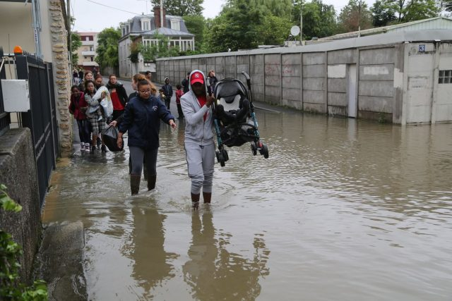Rue Foch, l'aide des jeuns du centre équestre permet à certaines personnes de se lancer pour une traversée de la zone inondée photo philippe serieys