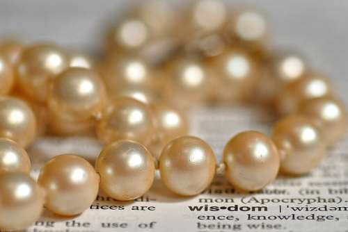 pearls on a newspaper with the word wisdom highlighted