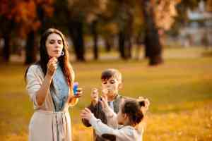 mom blowing bubbles with kids