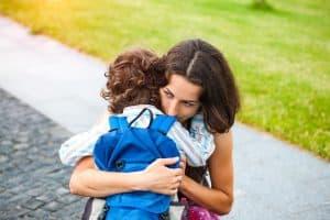 A woman is hugging a boy.