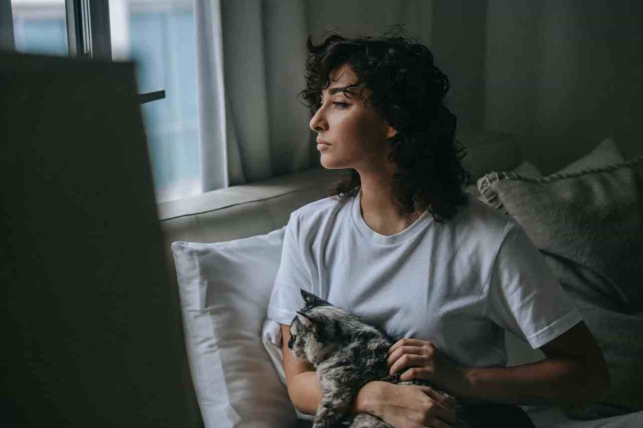 dreamy woman with soft kitty at home