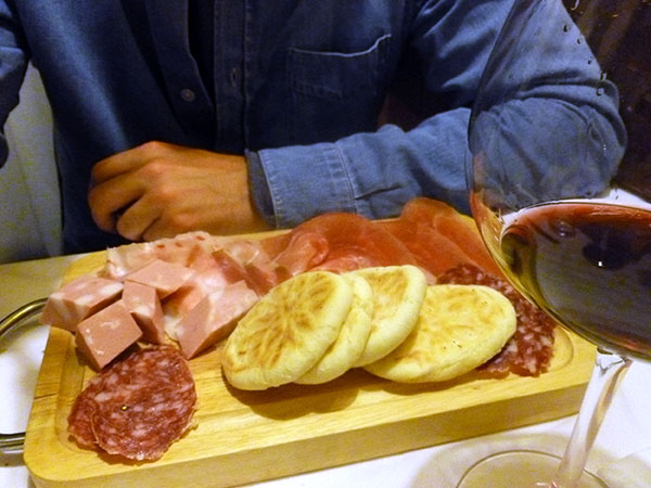Tigelle and meat on a platter, typical of Bologna cuisine.
