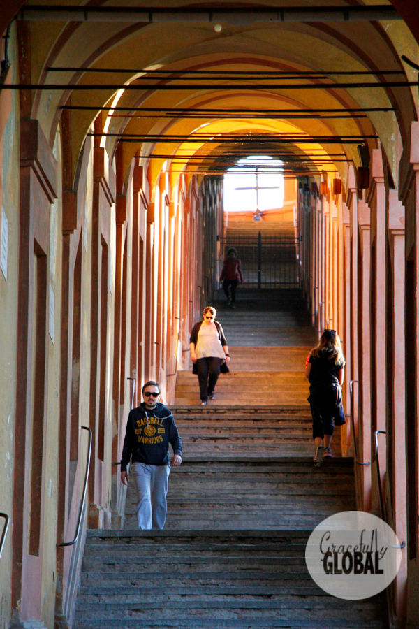 Tourists and locals walk to and from the Santuario della Madonna di San Luca on the long set of steps adorned by porticos.