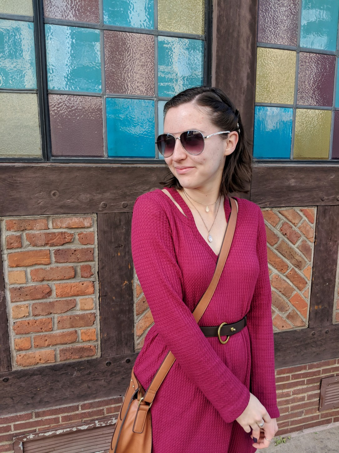 red v-neck dress with cutouts and aviator sunglasses