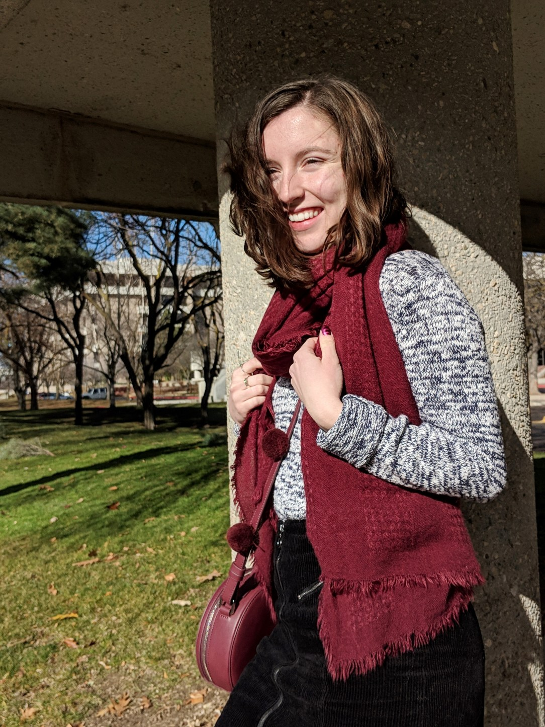 maroon scarf and maroon circle purse with pom poms