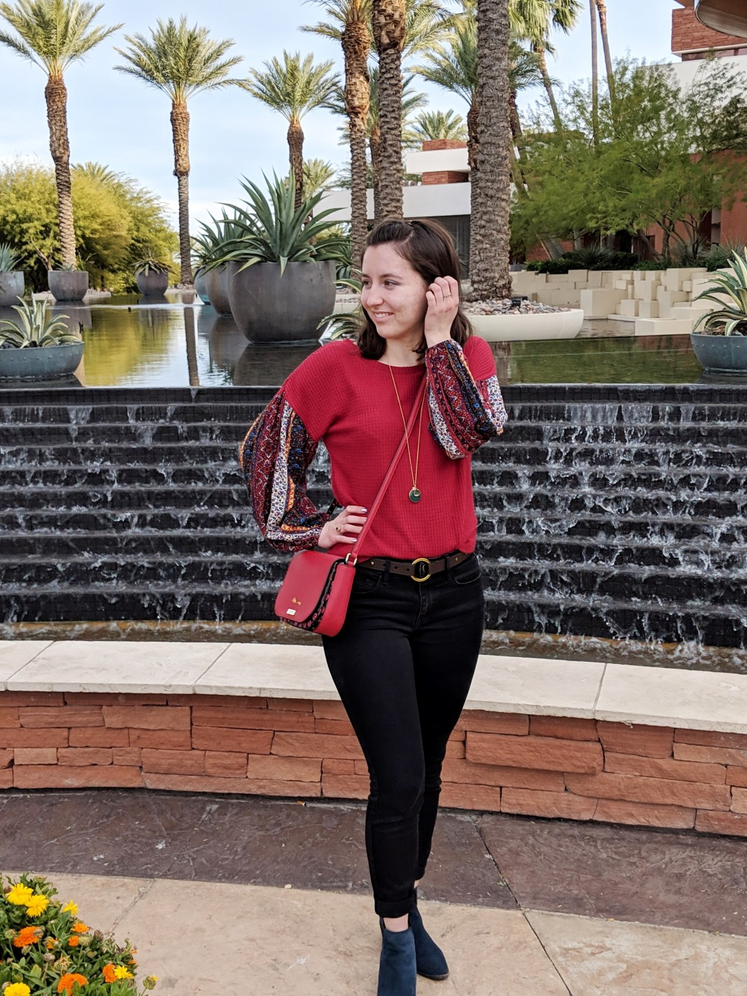 red patterned blouse black jeans red purse