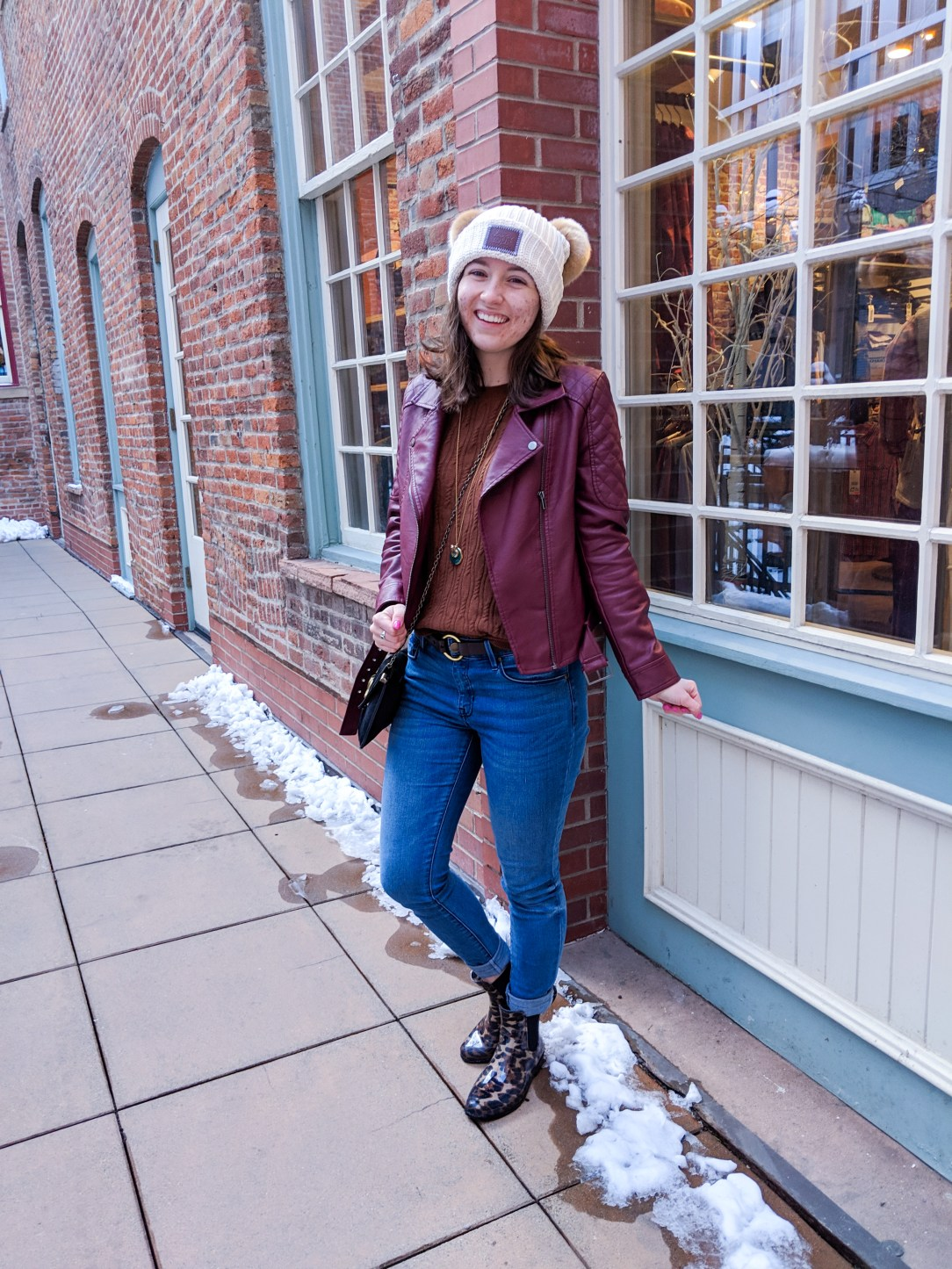 cream beanie, blue jeans, burgundy jacket, black purse, leopard boots