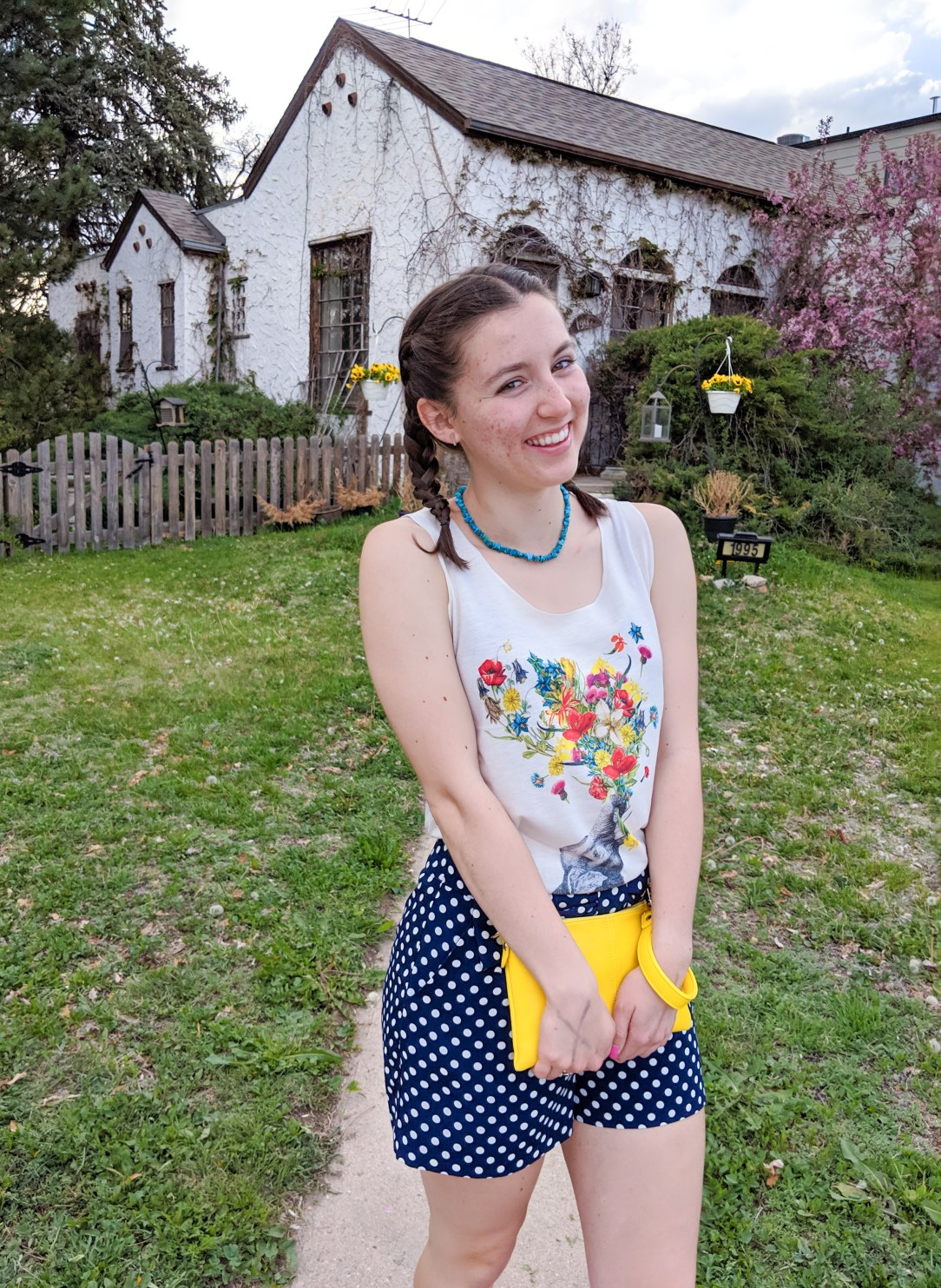 floral graphic tank top, yellow clutch, polka dot shorts, French braids