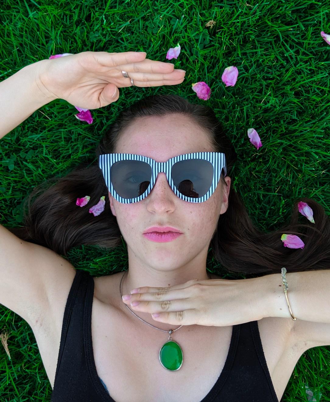rose petals, black dress, green necklace, striped sunglasses