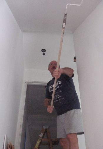 Ted paints a hard-to-reach area.