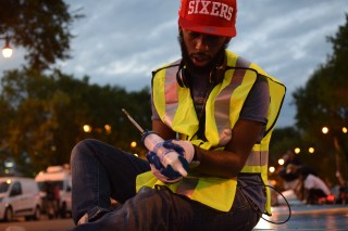 """Volunteer Johnny Jones helps install the mural """"14 Movements: A Symphony in Color and Words"""" on the median of Broad Street during July.   THE TEMPLE NEWS"""