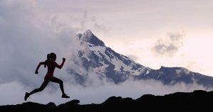 An athletic woman runs up a mountain.