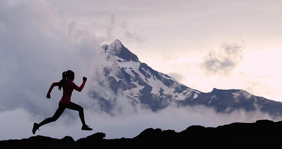 An athletic woman runs up a mountain