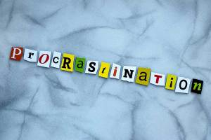 Cut letters spell procrastination on a grey marble background.