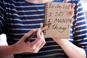 Woman's hand holding notebook that says: to do list 1. so 2. many 3. things