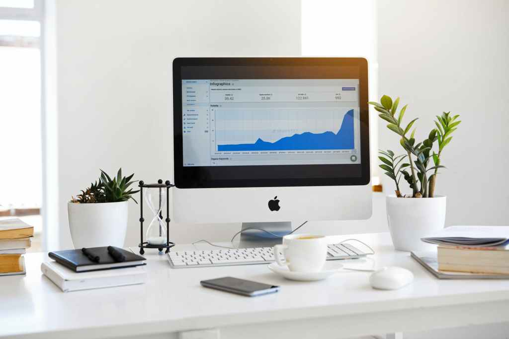 silver imac displaying line graph placed on desk (writing baiscs)