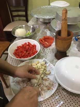 My mom dicing up some garlic to prepare a garlic-based seasoning for the goat.