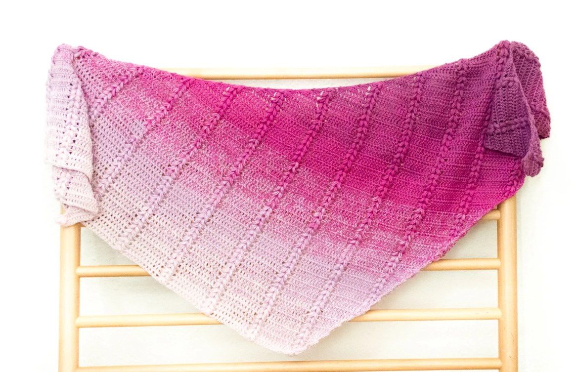 Pink to white gradient shawl draped over a wood grate