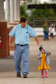 Jay Kimbrel, 60, of Bainbridge, Georgia, walks with his best friend's granddaughter, Margo Dean, 3, to watch the drill team competition at the Georgia National Fair in Perry, Georgia, on October 7, 2017. (Photo/Catherine Green)