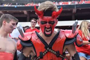 """Parker Wohl, 18, a business management major at the University of Georgia, participates as a member of the Spike Squad during the Georgia vs. Tennessee football game at Sanford Stadium, on September 29, 2018. Sitting field-level at Sanford Stadium, Wohl snarls aggressively and dons themed paint, spiked shoulder pads and other costume pieces to cheer for the dogs. Coming from a """"UGA family,"""" Wohl joined Spike Squad because he wanted to be around people as passionate about the Bulldogs as he was."""