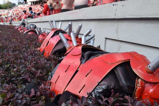 Several pairs of spiked shoulder pads sit on a hedge as members of the Spike Squad, a University of Georgia student group that cheers on the Georgia Bulldogs football team, apply paint during the Georgia vs. Tennessee football game on Sept. 29, 2018. The Spike Squad is named for the red and black shoulder pads adorned with spikes that they wear during each game.