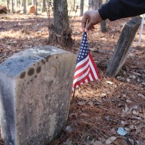 Linda Davis straightens a flag next to a solider's grave at Brooklyn Cemetery. (Photo/Caroline Kurzawa)
