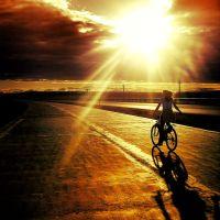 Kobieta na rowerze jedzie w kierunku słońca