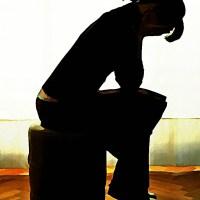 Zrozpaczona smutna kobieta siedząca  na stołku dłonie obejmują twarz