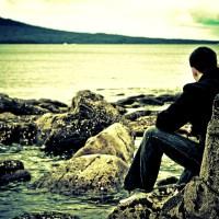 Siedzący mężczyzna na skałach jezioro woda Grafika Grafiki
