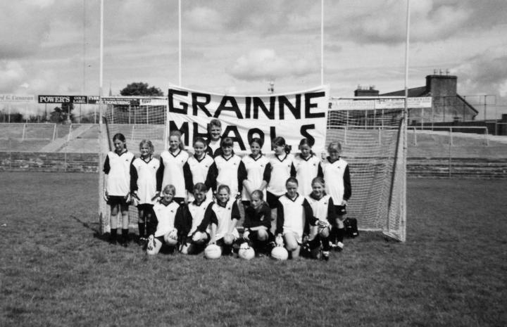 Grainne Mhaols U12s starting fifteen prior to the County A Championship Final on August 5th 2001 at Tuam Stadium; Back Row (l to r) Josephine McDonagh, Kim Young, Leigh Birchmore, Martha Folan, Paul Gannon (Coach/Manager), Becky Heanue, Tara Flaherty, Michelle Joyce, Aisling Kane and Jennifer Heanue. Front Row (l to r) Claire Mullen, Danielle Lydon, Noreen Coyne, Maire Staunton, Mary Joyce and Fionnuala Hannigan-Dunkley. This historic final served as a curtain raiser to the Connacht Junior Championship semi-final between Leitrim and Galway which was won by the hosts.