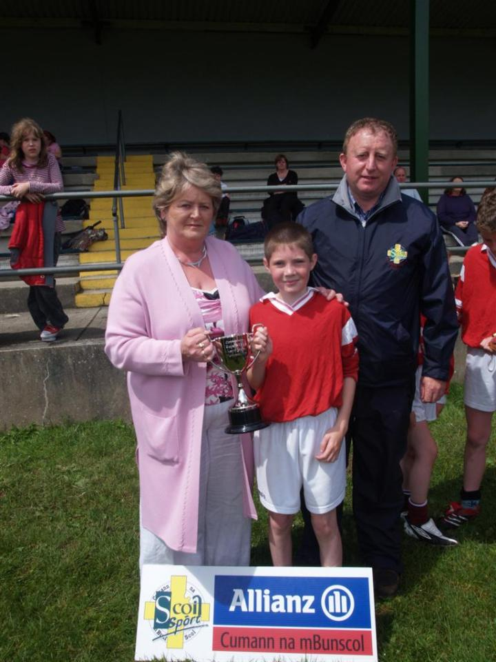 Caption for Photo of Kevin Joyce Cup Winnie Joyce Presents Callownamuck Captain Marcus McDonagh With The Kevin Joyce Cup With Gerry Hussey Of Cuman na mBunscoil