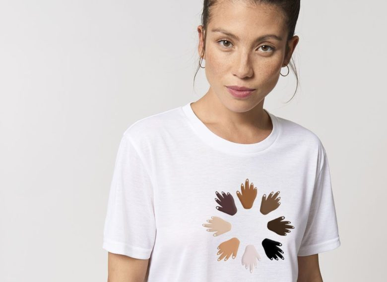 A woman wearing the new 'Reaching out' t-shirt. The t-shirt features hands, of varying colours, in a circle.