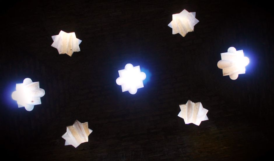 Inside the baños arabes at the Alhambra looking up through the star shaped skylites