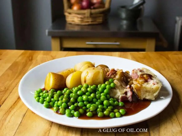 bacon and onion pudding served with new potatoes and peas